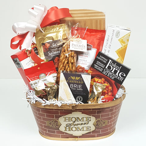 A perfect housewarming gift basket with a chockfull of delectable treats complete with a cheese board to keep, pretzels and chocolates, crackers, cheese, smoked salmon and cookies to eat.