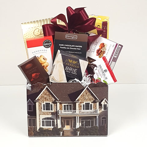 A beautiful house box gift basket filled with crackers and cheese and sweet treats to eat.