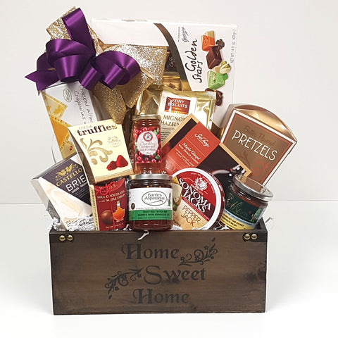 A beautiful wood housewarming gift basket crate holds chocolates, cheese, crackers, red pepper jelly, smoked salmon, cookies and lots more.