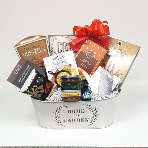 A keepsake tin housewarming gift filled with crackers and cheese, salsa, dip mix, chocolates, pretzels & more.