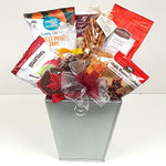 A pretty silver planter gift basket loaded with sweet potato chips, maple roasted cashews, Martin's apple chips, pretzels, chocolates, peanut brittle and more.