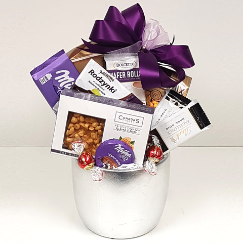 A silver ceramic pot gift basket nestled with Lindt chocolate, chocolate covered raisins, a salty snack mix, chocolate treats, wafer rolls and pretzels too!