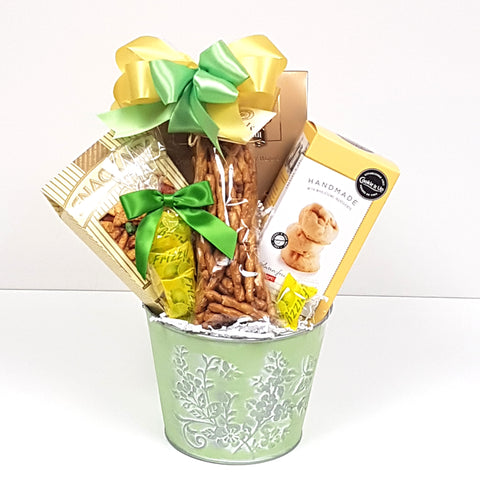 A pretty tin get well gift basket filled with lots of yummy sweet and salty snacks.
