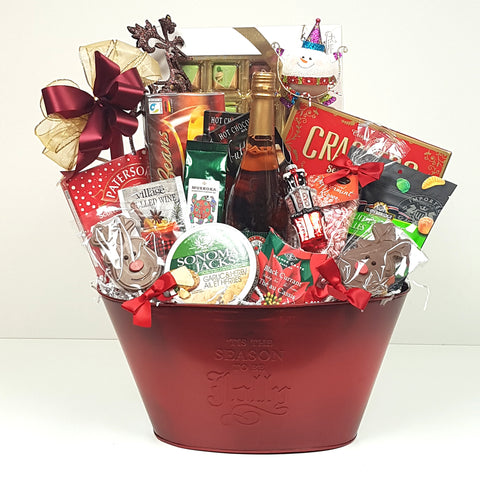A special Christmas gift basket loaded with sweet and salty treats, cheese, sparkling cider, crackers, coffee, tea and a couple keepsake ornaments.