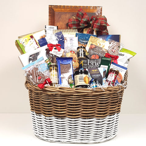A hamper Christmas gift basket filled with delectable gourmet toppings, jellies, mustards, olives, cheese, crackers and smoked salmon bites along with loads of delicious goodies for the sweet tooth and salty lover too!