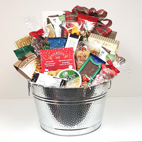 A shiny silver tub Christmas gift basket with cheese, crackers, a delectable assortment of chocolates, cookies, salt water taffy, snack mix, nuts, pretzels and loads more.