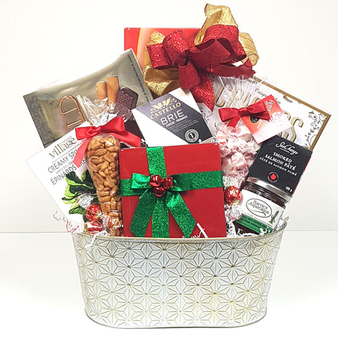 A  starburst white and gold tin Christmas gift basket holding tasty chocolates, cookies, smoked salmon pate, crackers, cheese, nuts, Salsa, salt water taffy and a pretty ceramic keepsake Christmas box.