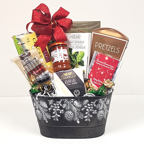 A pretty pinecone tin Christmas gift basket loaded with cheese, crackers, dip mix, cookies, pretzels, sundried tomato pate, pepperoni and mustard too.