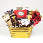 A sparkly gold tin gift basket brimming with all things chocolate. There's chocolate maple caramel crunch, chocolate covered cherries, chocolate seashells, chocolate truffles, hot chocolate and still more.