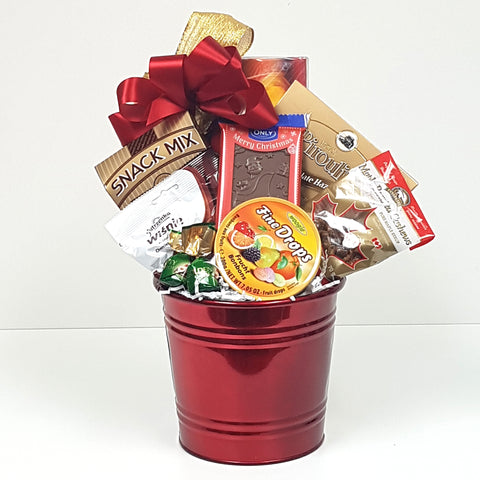 A pretty red tin Christmas gift basket filled with a tasty snack mix, maple roased cashews, chocolate covered cherries, fruit bonbons and more.