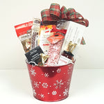 A snowflake tin Christmas gift basket brimming with delicious Canadian sweet and savoury treats like smoked salmon, crackers, red pepper jelly, peppermint candy kisses and Canada True maple popcorn to name a few.