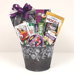 A pretty acorn tin Christmas gift basket loaded with coffee, tea, mulled wine mix, chocolates and other sweet treats to eat.