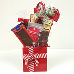 A ceramic Christmas gift box holding Christmas chocolate gems, chocolate filled wafers, chocolate almonds and more.
