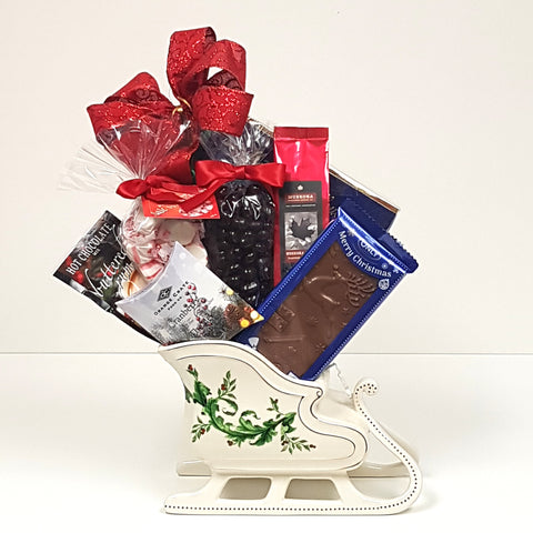 A beautiful ceramic sleigh gift basket filled with chocolates, sweets, coffee and tea.