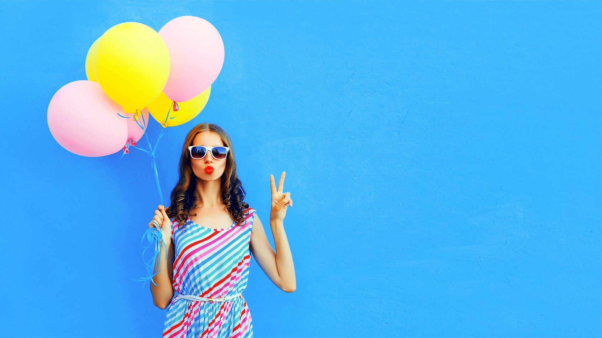 Woman holding colorful balloons against blue wall