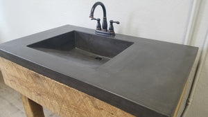 Concrete vanity top with integral ramp sink