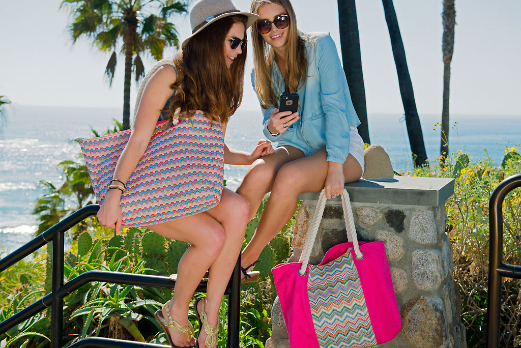 Girls having fun at the beach with their colorful beach bags