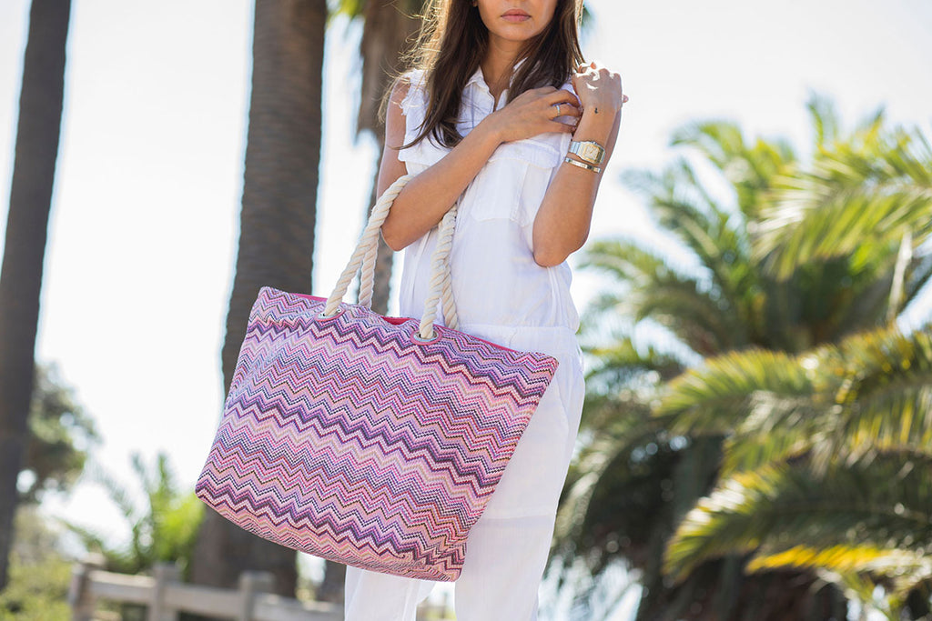 Woman in a park wearing a pink nylon beach tote