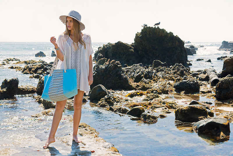 women at the beach with her pastel blue makaron beach bag