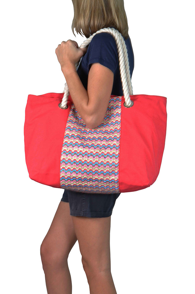 model with a raspberry red canvas beach bag, shoulder handles