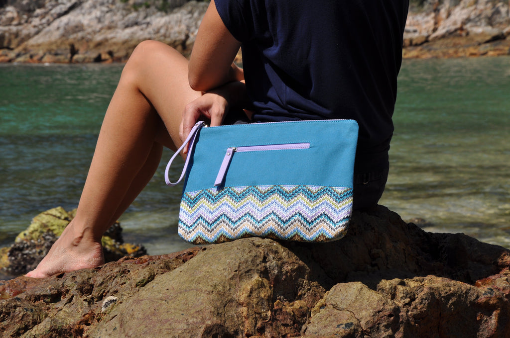 woman at the beach with her blue, teal and purple cosmetic travel bag