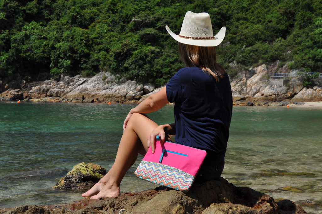 Woman at the beach with a pink MAKARON beach pouch on her side