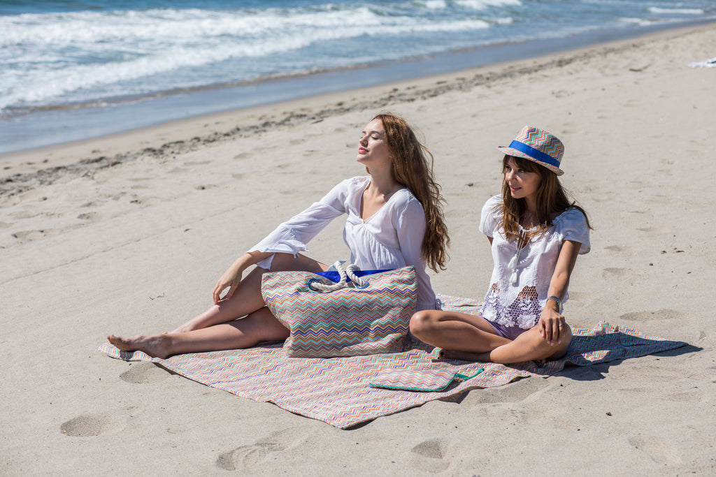 Girls laying down the beach on a sand free beach mat