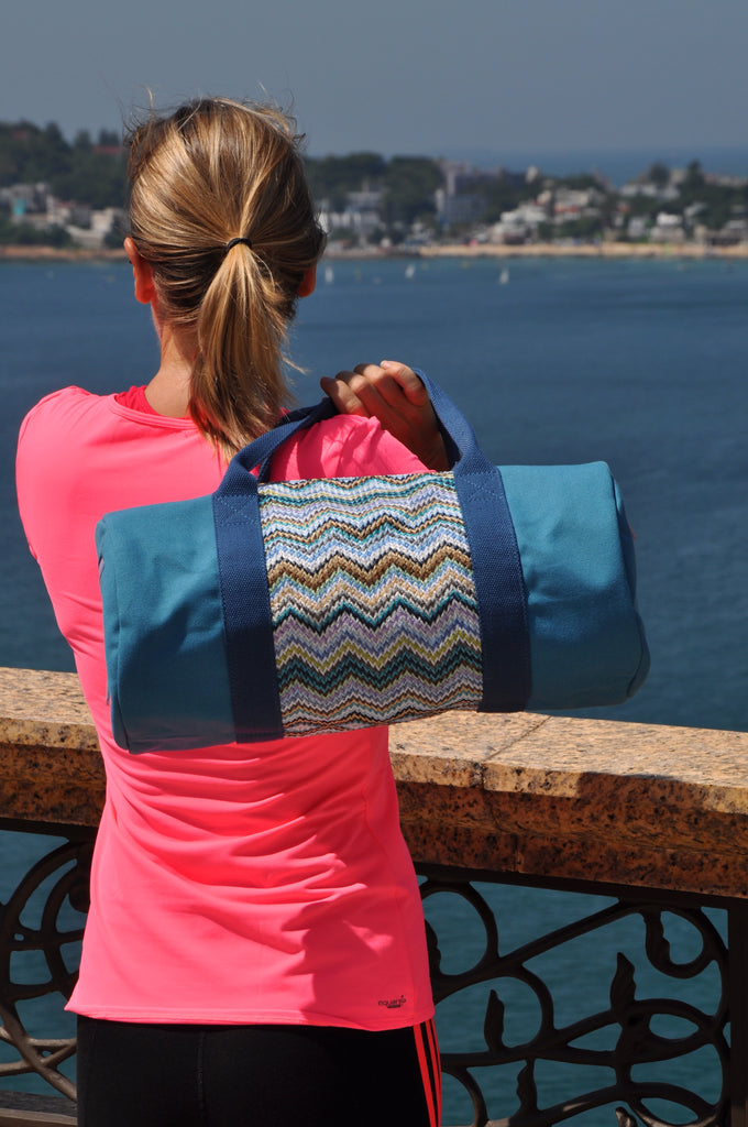 Girl watching the sea and carrying a blue canvas and nylon gym bag