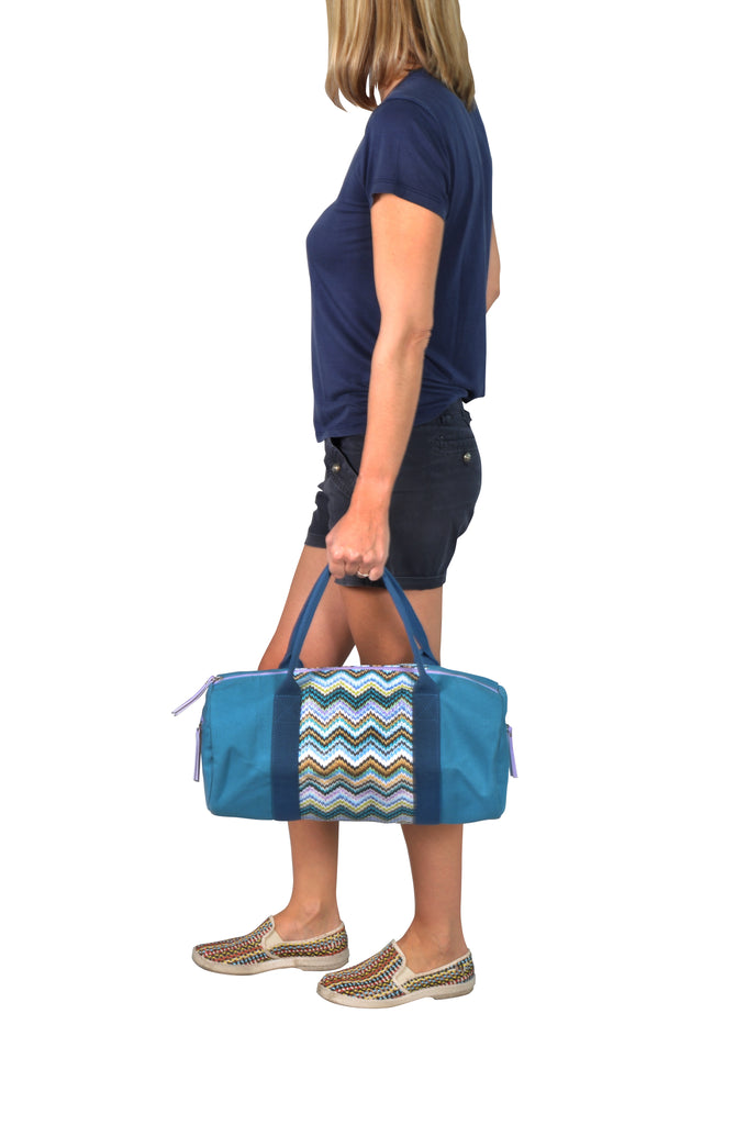 woman carrying a blue canvas gym tote bag