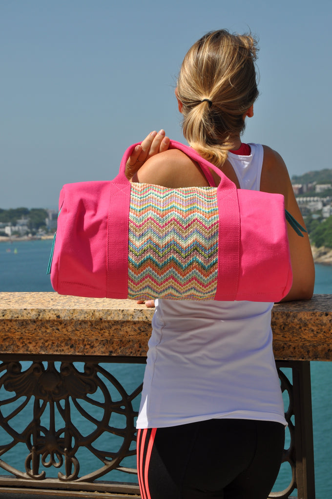 woman watching the sea with a pink nylon gym bag