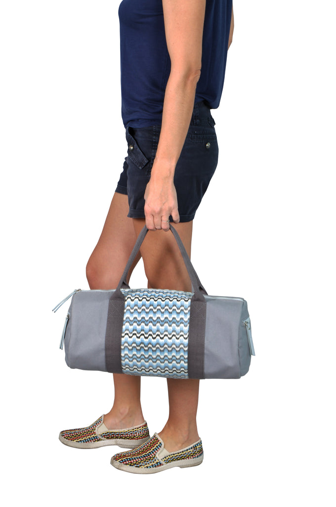 woman carrying a grey gym bag
