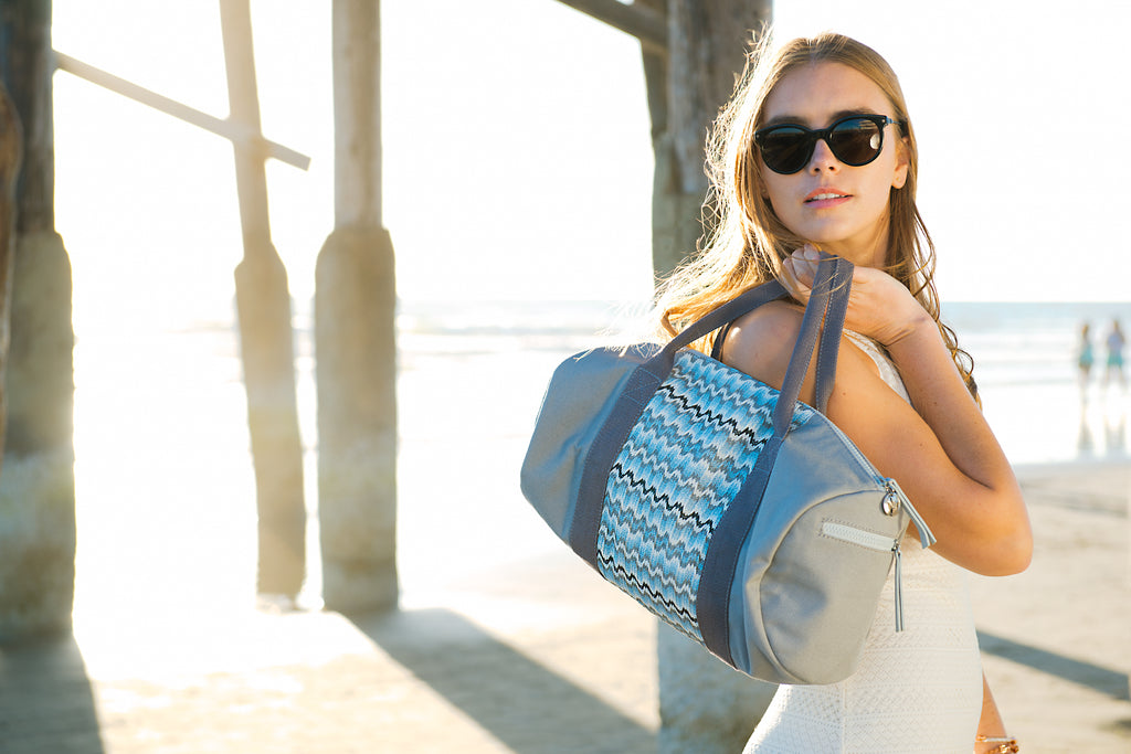 Blond women at the beach with a nylon gym tote bag