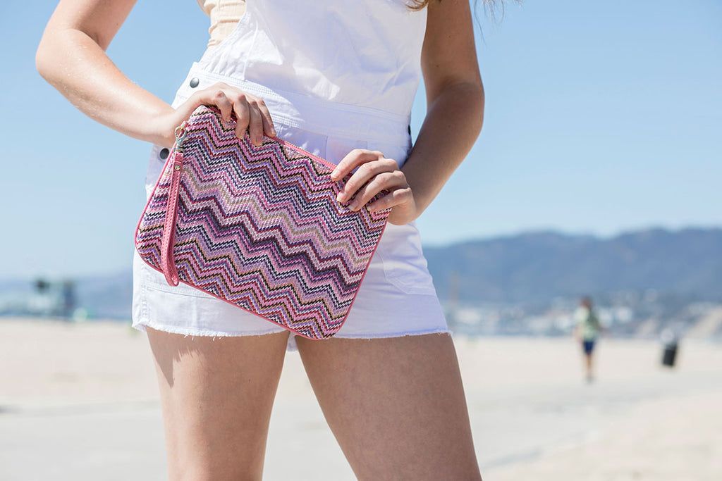 Model at the beach with a pink zigzag pouch with wrist strap