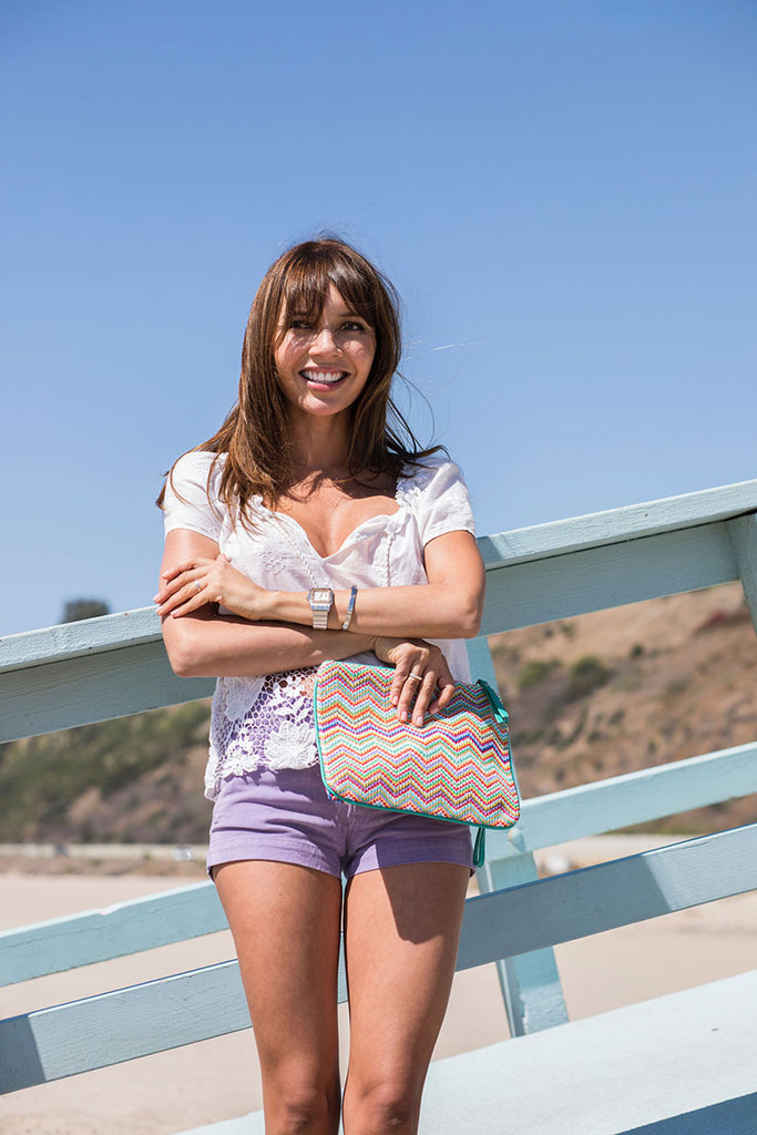 Girl smiling at the beach carrying a pouch