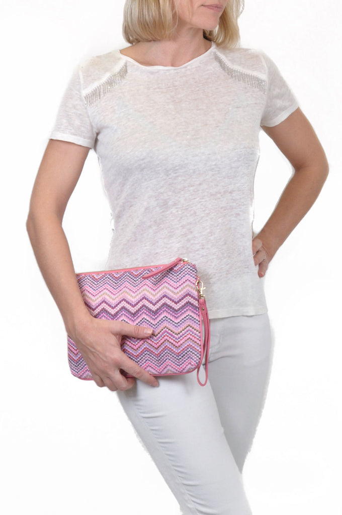 woman carrying pink clutch with zigzag design