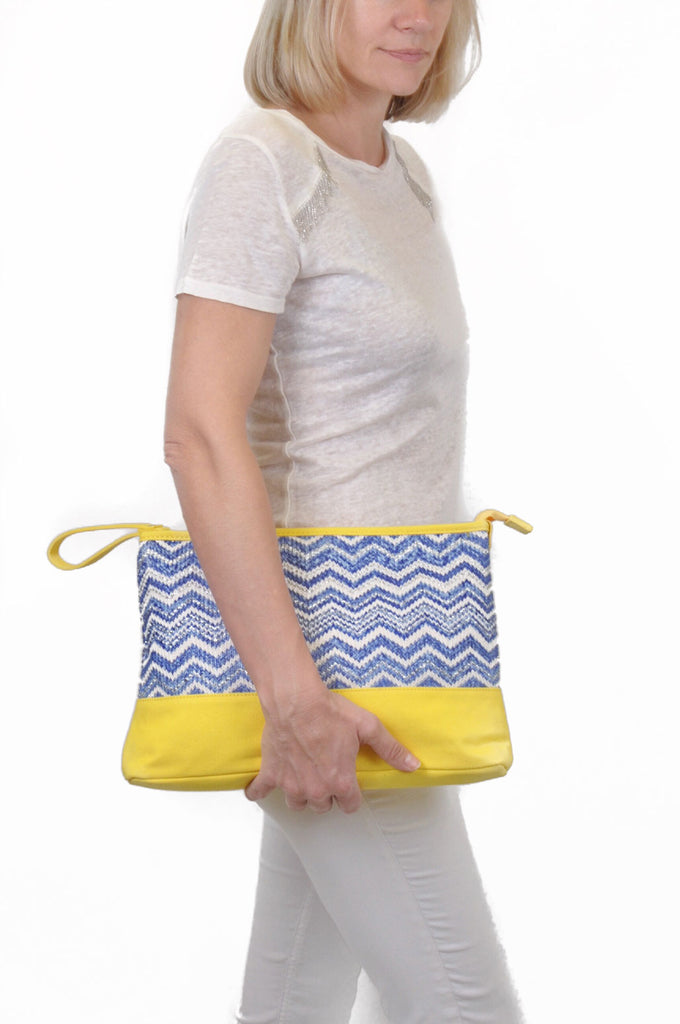model wearing a cosmetic travel pouch in blue and yellow patterns