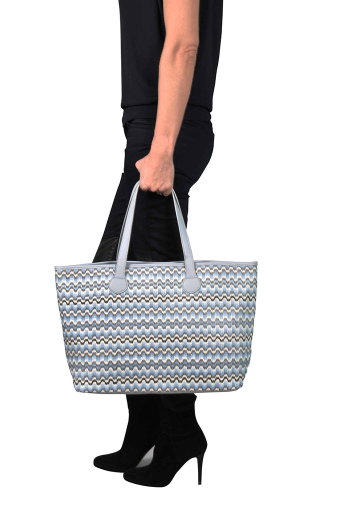 woman wearing a grey and blue zigzag shoulder tote bag