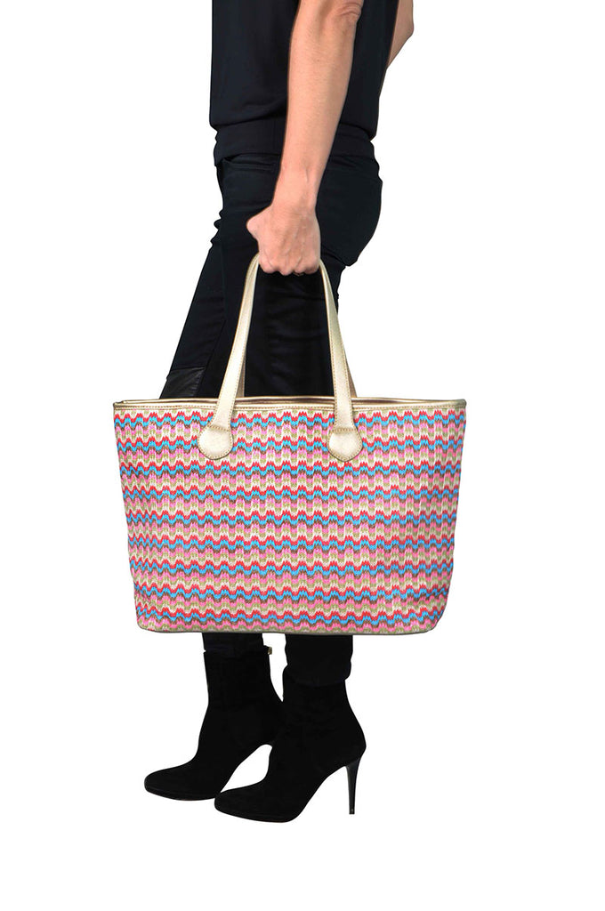 woman wearing a pink and gold travel tote bag