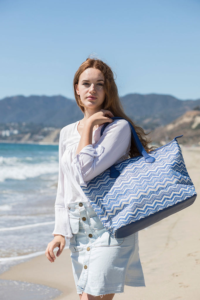 woman carrying a blue shoulder tote bag