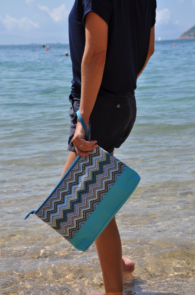 woman at the beach carrying a blue cosmetic travel bag