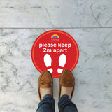 Person standing on Please keep 2 metres part high school red floor sticker