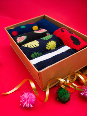 A gold box containing the spotty, tricolour, watermelon, monstera leaf, stripey and red leopard print organic kind socks. The box is surrounded by gold ribbon and pink and green pom poms and is displayed on a bright red backdrop.