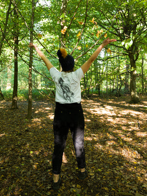 An individual wearing the organic 'footprints' tee facing away from the camera standing in a forest and throwing leaves into the air