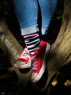 An individual is wearing the navy blue and white striped organic kind socks with red converse and blue jeans whilst standing in a tree with sunlight shining on their feet.