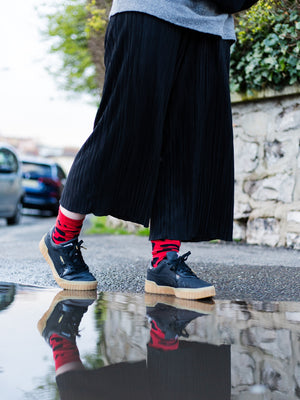 An individual is walking past a puddle in the street in black trousers and trainers, wearing the bold red leopard-print organic kind socks. The reflection of their socks is clearly visible in the puddle.