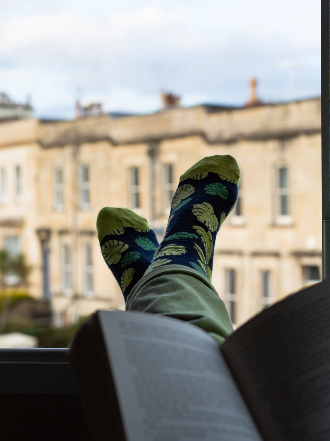 An individual wearing the organic monstera leaf kind socks  with their feet hanging out of the window whilst reading a book