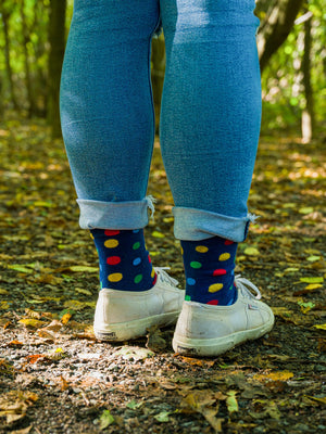 An individual wearing the navy blue organic kind socks with bright multicolour spots and white plimsolls in a forest with autumn leaves surrounding their feet.