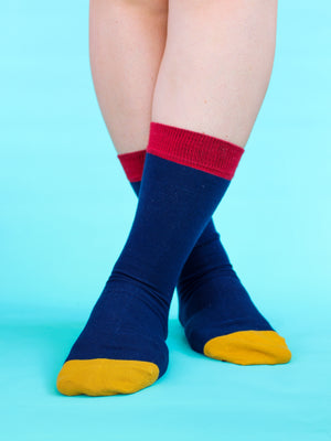 Navy organic socks with a mustard yellow toe patch and a red ankle trim. Modelled by an individual who is crossing their feet over and is stood in front of a teal backdrop.