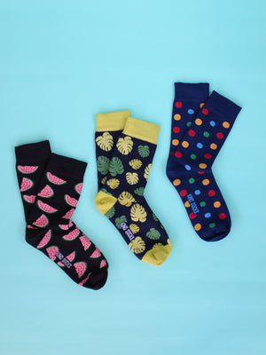 Black organic socks with a pink watermelon print, black organic socks with green monstera leaves and a green ankle, heel and toe trim and navy blue organic socks with a multicolour spot pattern are laid out in a diagonal pattern on a teal blue backdrop.