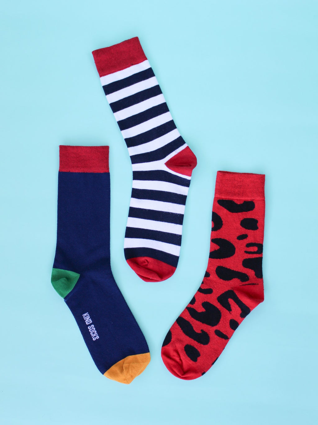 Navy blue organic kind socks with a mustard toe, lime green heel and red ankle trim, navy blue and white striped organic kind socks with a bright red trim and bold red organic kind socks with a black leopard-print design and laid out on a teal blue backdrop.
